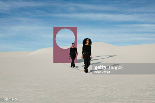 female models walking on white sand dunes against portal at desert - purple pants stock pictures, royalty-free photos & images