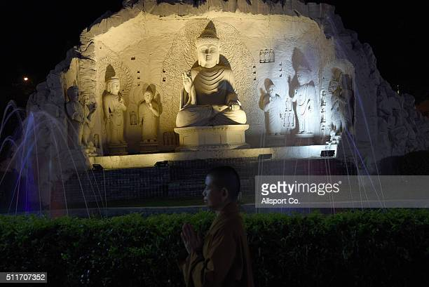 A female monk offers prayers near Buddha statues at the Fo Guang Shan Dong Zen Temple to celebrate the Lantern Festival on the last day of Chinese...