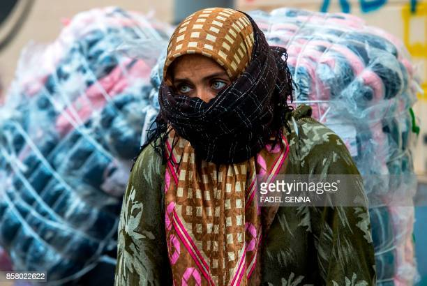 A female Moroccan porter carries a bundle of goods on her back to transport across the ElTarajal border from Spain's North African exclave of Ceuta...