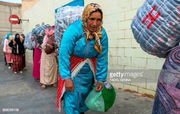 Female Moroccan porters carry bundles of goods on their backs to transport across the ElTarajal border from Spain's North African exclave of Ceuta...