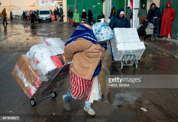 Female Moroccan porters use trolleys to transport bundles of goods across the El-Tarajal border from Spain's North African enclave of Ceuta into...