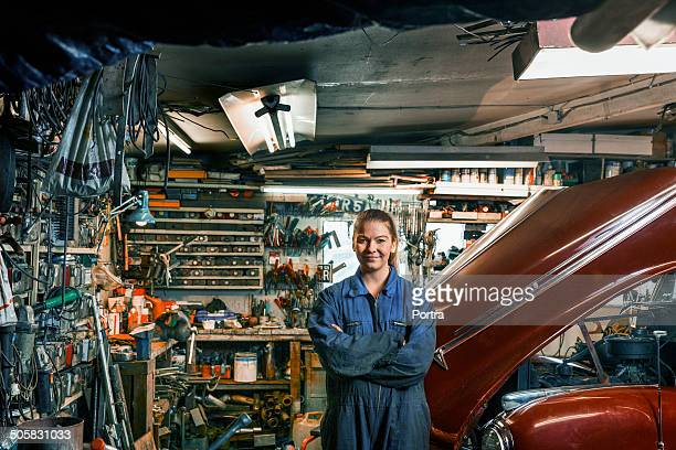 female motor mechanic standing in a garage. - mechanic stock pictures, royalty-free photos & images