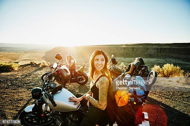 Female motorcyclist at overlook during road trip