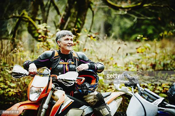 Female motorcyclist in discussion with friends after riding dirt bikes