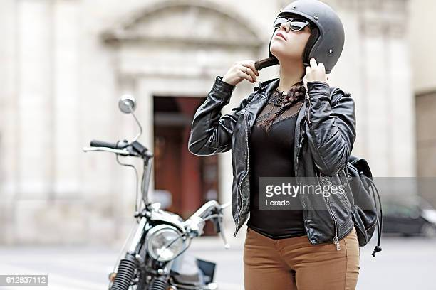 Female motorcyclist preparing for a ride on a vintage motorbike