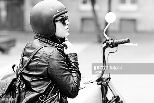 female motorcyclist preparing for a ride on a vintage motorbike - women black and white motorcycle stock pictures, royalty-free photos & images
