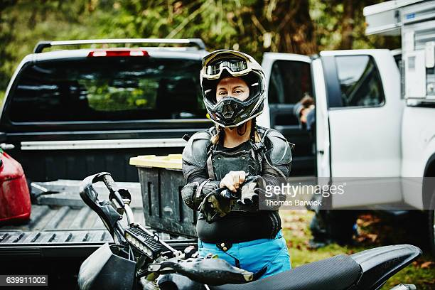 Female motorcyclist putting on gloves before riding dirt bike with friends