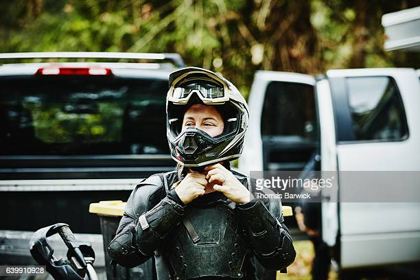 Female motorcyclist putting on helmet before riding dirt bike with friends