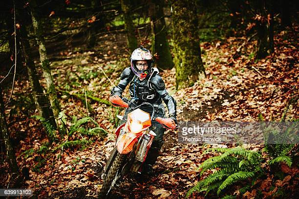 Female motorcyclist riding dirt bike on forest trail on fall afternoon