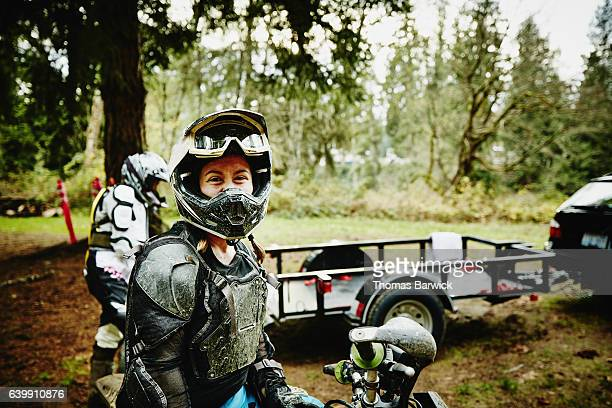 female motorcyclist smiling after riding dirt bikes with friends - motocross fotografías e imágenes de stock