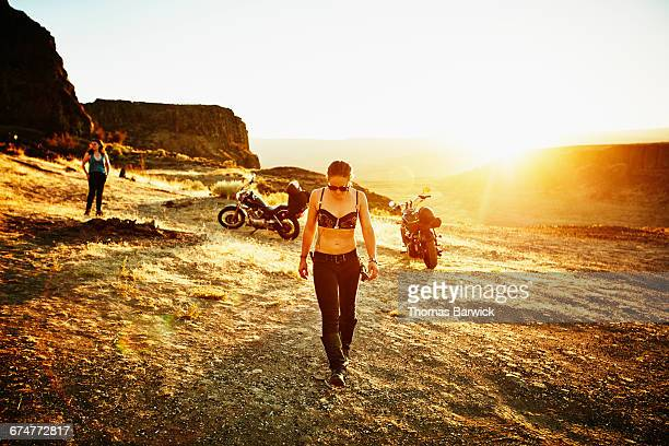 Female motorcyclist walking through camp at sunset