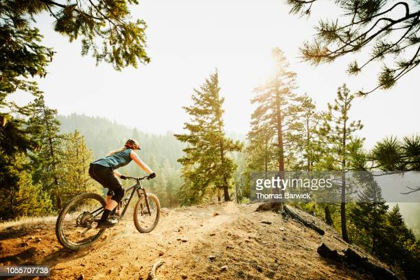 female mountain bike rider descending on mountain ridge on summer evening - bicycle trail outdoor sports stock photos and pictures