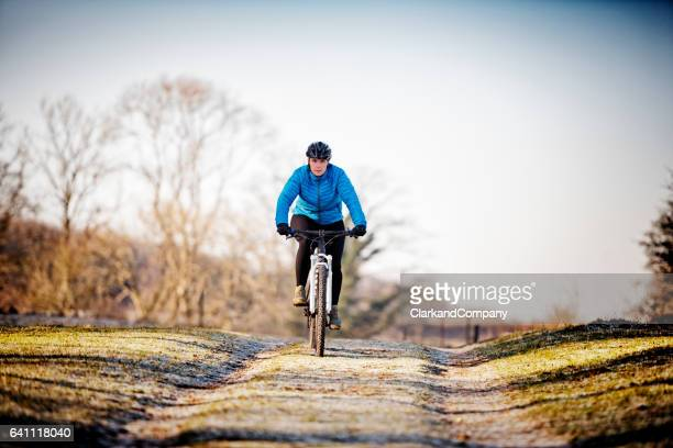 female mountain bike rider out for a training ride. - bicycle trail outdoor sports stock photos and pictures
