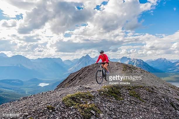 Female mountain biker descends ridge crest