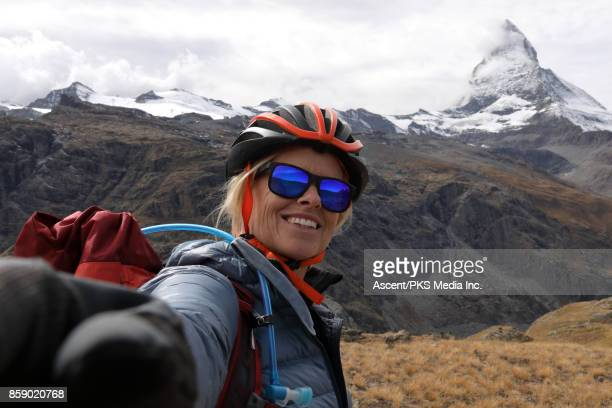 female mountain biker pauses in alpine meadow, below matterhorn - one mature woman only stock pictures, royalty-free photos & images