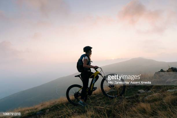 female mountain biker pauses in alpine track, sunrise - mountain biking stock pictures, royalty-free photos & images
