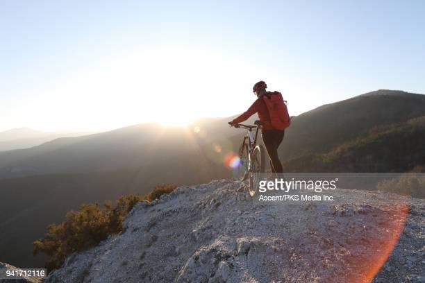 Female mountain biker pushes bike to rock summit