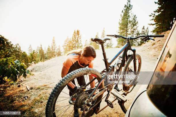 Female mountain biker putting bike on car after ride on summer evening