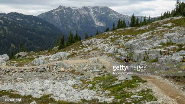 female mountain biker rides through high alpine environment - ascent xmedia stock pictures, royalty-free photos & images