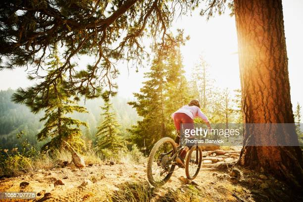 female mountain biker riding down ridgeline trail on summer evening - bicycle trail outdoor sports stock photos and pictures