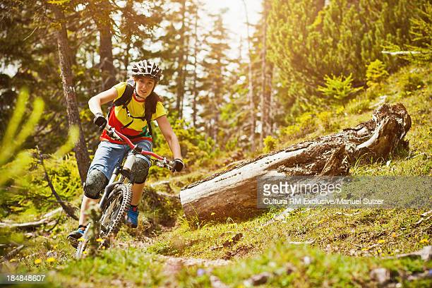 Female mountain biker riding through forest