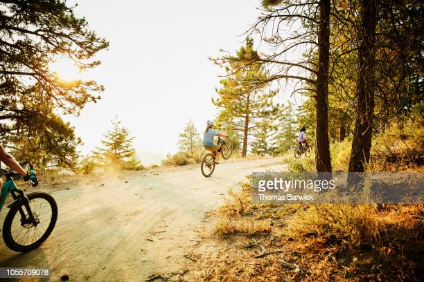 Female mountain biker riding wheelie on forest road on summer evening