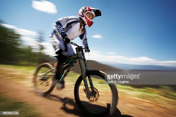 Female mountain biker speeding down dirt track