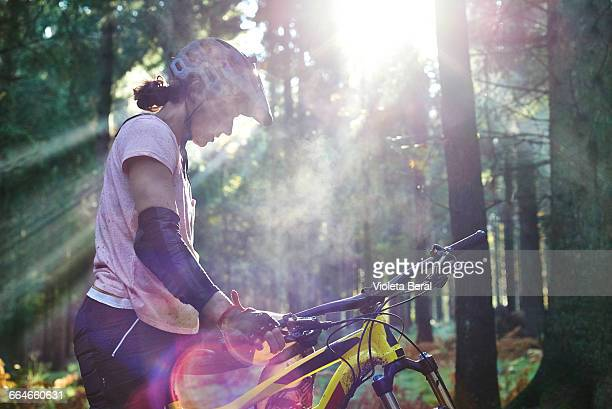 Female mountain biker standing in sunbeam with head down, Forest of Dean, Bristol, UK