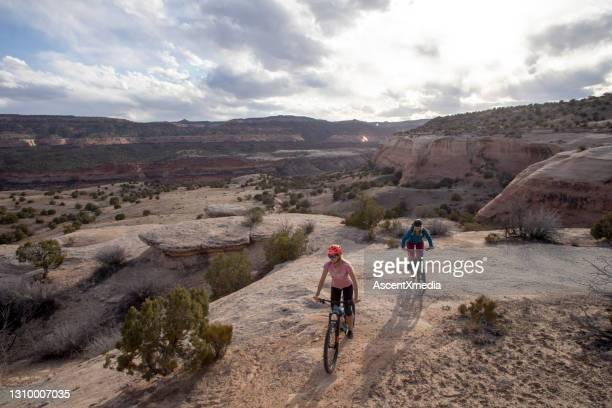 mountain bikers seguem caminho do deserto pela manhã - planalto - fotografias e filmes do acervo