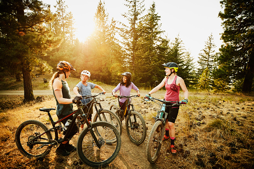 Female mountain bikers in discussion after descending mountain trail - gettyimageskorea