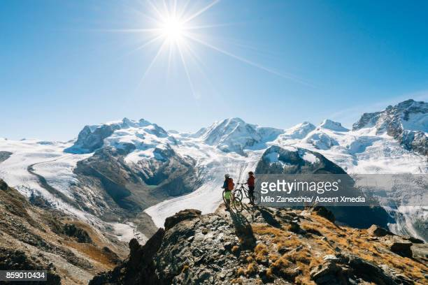 female mountain bikers look off to snow capped mountain range, from edge - snowcapped mountain stock pictures, royalty-free photos & images