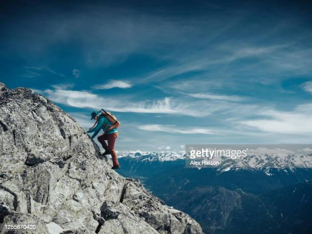 female mountain climber ascends an exposed rock ridge high above the valley - bc stock pictures, royalty-free photos & images