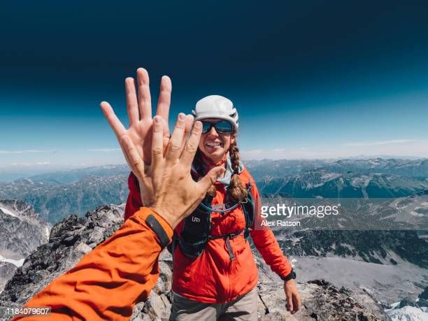 female mountain climber high fives her combing partner at the summit - high five stock-fotos und bilder