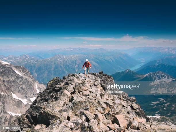 female mountain climber hiking along the summit ridge of mount matier - スクランブリング ストックフォトと画像