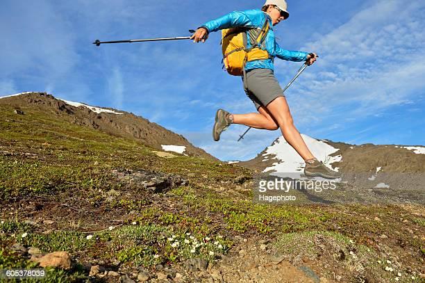 Female mountain climber jumping downhill, Chugach State Park, Anchorage, Alaska, USA
