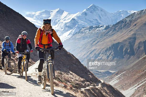 female mountainbike leader on annapurna circuit, nepal - annapurna conservation area stock photos and pictures