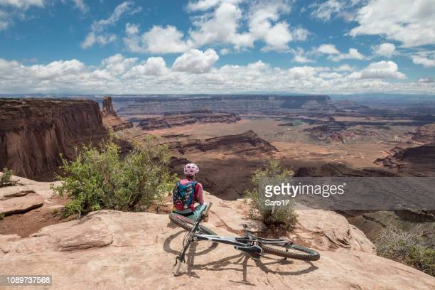 female mountainbiker at dead horse point state park viewpoint, moab, utah. - dead horse point state park stock pictures, royalty-free photos & images