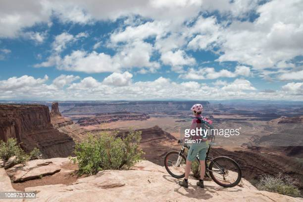 female mountainbiker at scenic viewpoint in dead horse point state park, utah. - dead horse point state park stock pictures, royalty-free photos & images
