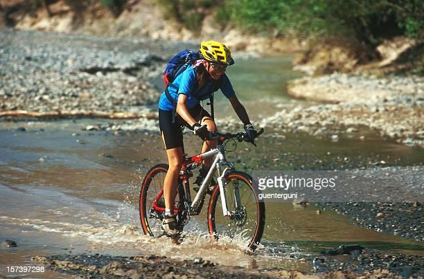Femme Mountainbiker traverse un ruisseau