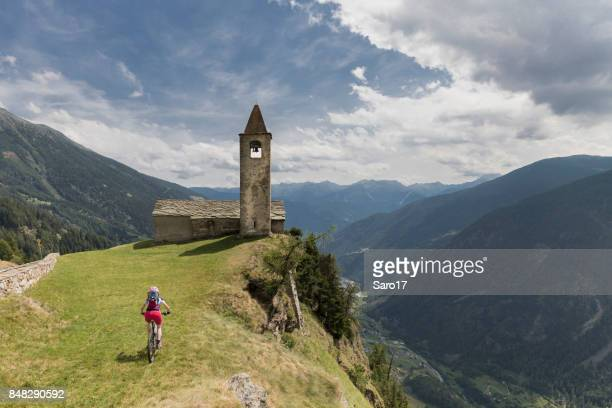 Female mountainbiker is approaching the little church of San Romerio, Switzerland.