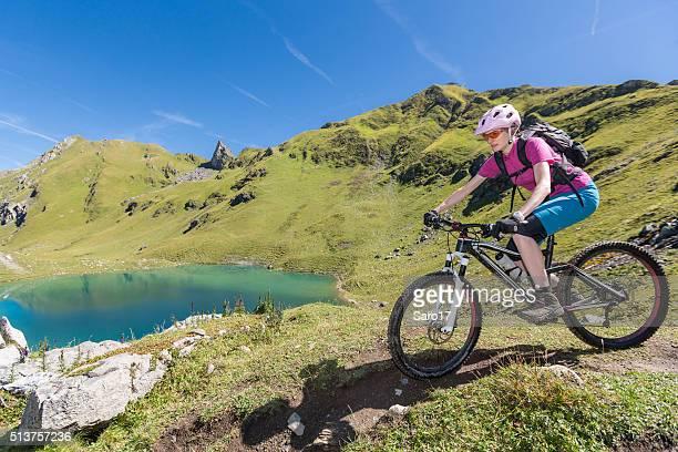 Female mountainbiker is approaching Urdensee, Switzerland