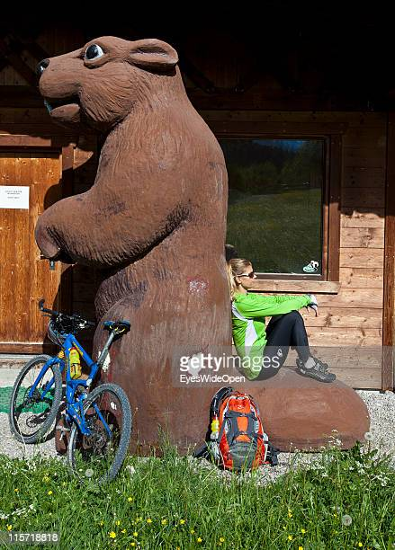 Female Mountainbiker is taking a nap at the tail of a giant beaver statue on May 26 2011 in Biberwier Lermoos Austria Lermoos is located next to the...