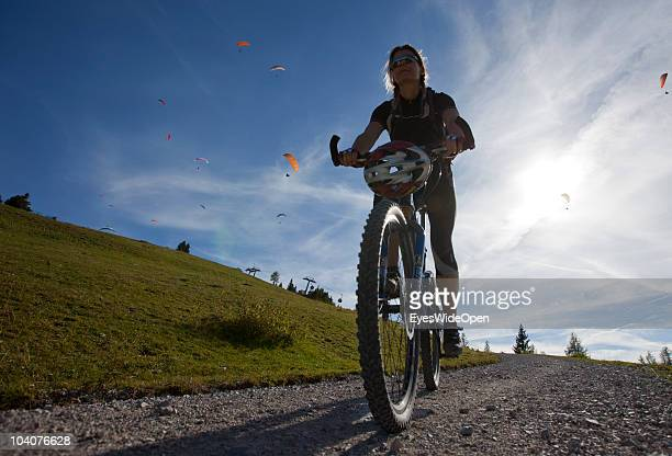 A female mountainbiker riding downhill the Unterberg Mountain while paragliders are flying on September 12 2010 in Koessen Austria