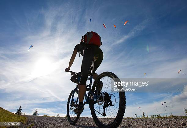 A female mountainbiker riding uphill the Unterberg Mountain while paragliders are flying on September 12 2010 in Koessen Austria