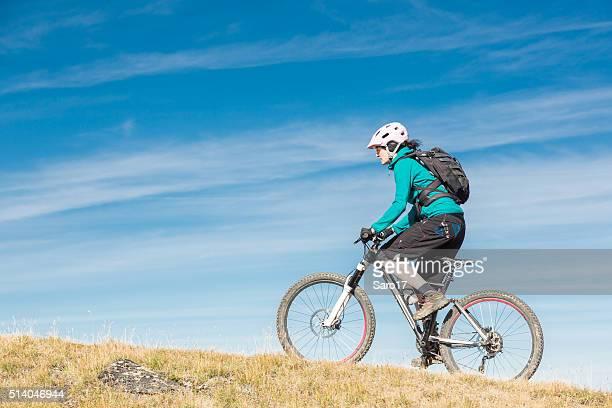 Weibliche Mountainbiker bergauf, Schweiz