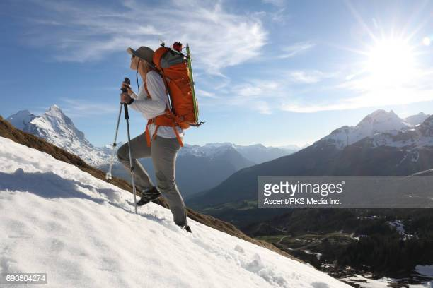 female mountaineer ascends snowslope above valley, mtns - leanincollection stock pictures, royalty-free photos & images
