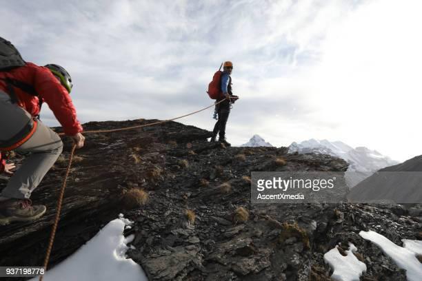 female mountaineer climbs to summit belay - alpinismo foto e immagini stock