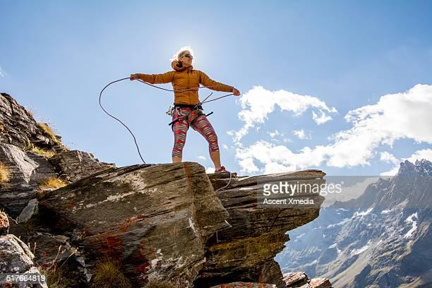 Female mountaineer coils rope on mountain ridge
