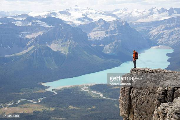 Female mountaineer pauses on ridge, lake below
