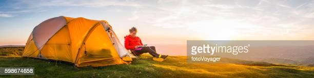 Female mountaineer relaxing beside tent idyllic summer sunset peak panorama
